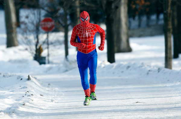 Patrick O'Brien jogs around Lake Harriet in south Minneapolis in a Spiderman wind suit, January 6, 2014. A blast of Arctic air gripped the mid-section of the U.S. on Monday, bringing the coldest temperatures in two decades, forcing businesses and schools to close and causing widespread airline delays and hazardous driving conditions. REUTERS/Eric Miller (UNITED STATES - Tags: ENVIRONMENT TPX IMAGES OF THE DAY) - RTX174A3