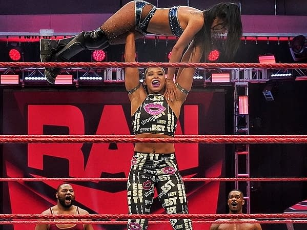 As The Street Profits look on, Bianca Belair presses Zelina Vega over her head on Raw, courtesy of WWE.