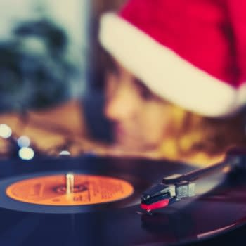 Blurred Image of Christmas. Turntable vinyl record player. Sound technology for DJ to mix & play music. Blurred a girl in a Christmas cap with red hair listening to a vinyl record in the background