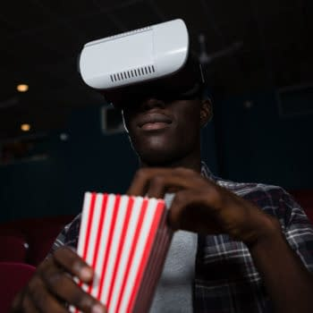 Man using a virtual reality headset while watching a movie in a theatre. By wavebreakmedia/Shutterstock