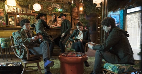 Zombie apocalypse survivors Columbus, Wichita, and Flagstaff turn Magic: The Gathering cards sideways in Zombieland: Double Tap (2019), while Tallahassee, Albuquerque, and Nevada look on. (Image attributed to Columbia Pictures)