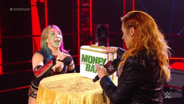 Becky Lynch presents the WWE Raw Women's Championship to Asuka, courtesy of WWE.