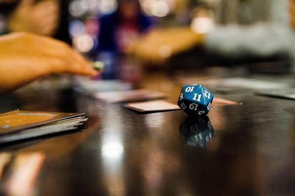 A promotional photograph showing a game of Magic: The Gathering. Source: magic.gg