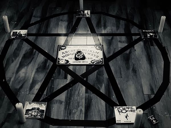 A photographic still from My Chemical Romance, featuring their albums in a summoning pentagram.