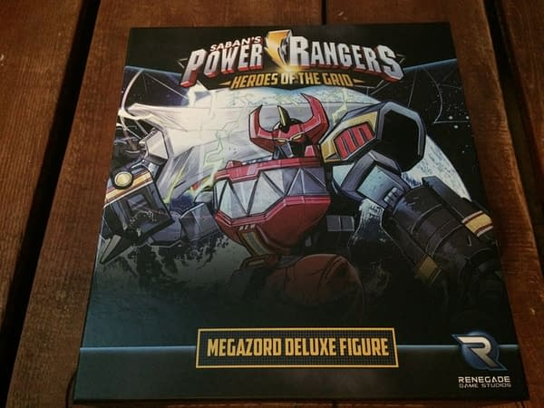 The front lid of the box for Renegade Game Studios' Megazord deluxe figure for the Power Rangers: Heroes of the Grid board game.
