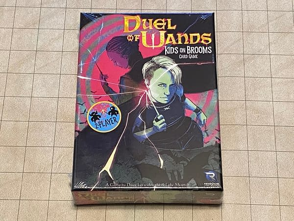 The front cover of the box for Duel of Wands, a card game based in the world of the Kids on Brooms RPG, both games developed by Renegade Game Studios.
