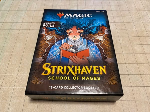 The packaging for the Collector Booster packs from Magic: The Gathering's Strixhaven: School of Mages expansion set. Note that the squares on the grid background are in inches.