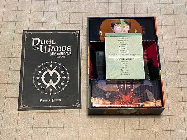 The full gamut of the component contents of the Duel of Wands card game by Renegade Game Studios includes 45 cards for gameplay, two spell reference cards, and a rulebook.