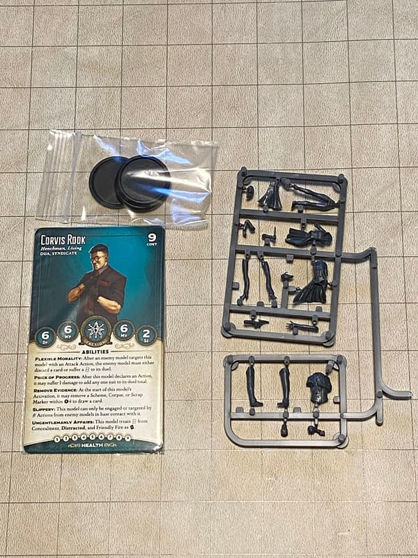 An array of the components you'd see in the Dirty Work boxed set for Wyrd Miniatures' game Malifaux.