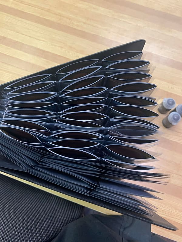 A picture from Reddit, allegedly of a foil-filled Magic: The Gathering binder of Commander Legends cards, all hopelessly arching from curling. Source: Reddit